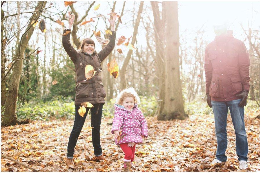 family throwing leaves in hockley woods, essex