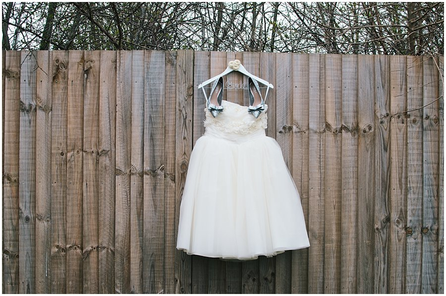 wedding dress and shoes hanging on a fence