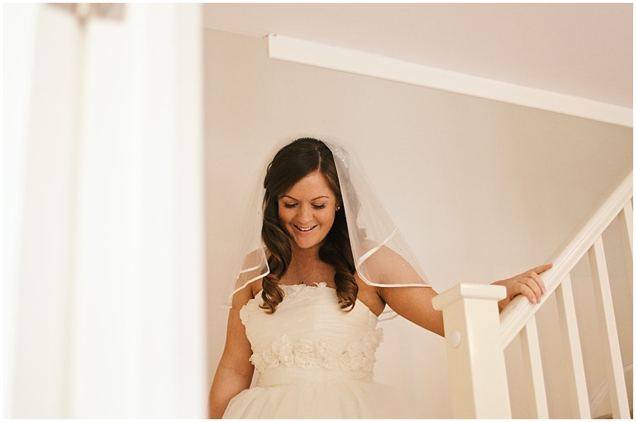 bride coming down the stairs at her house in southend-on-sea