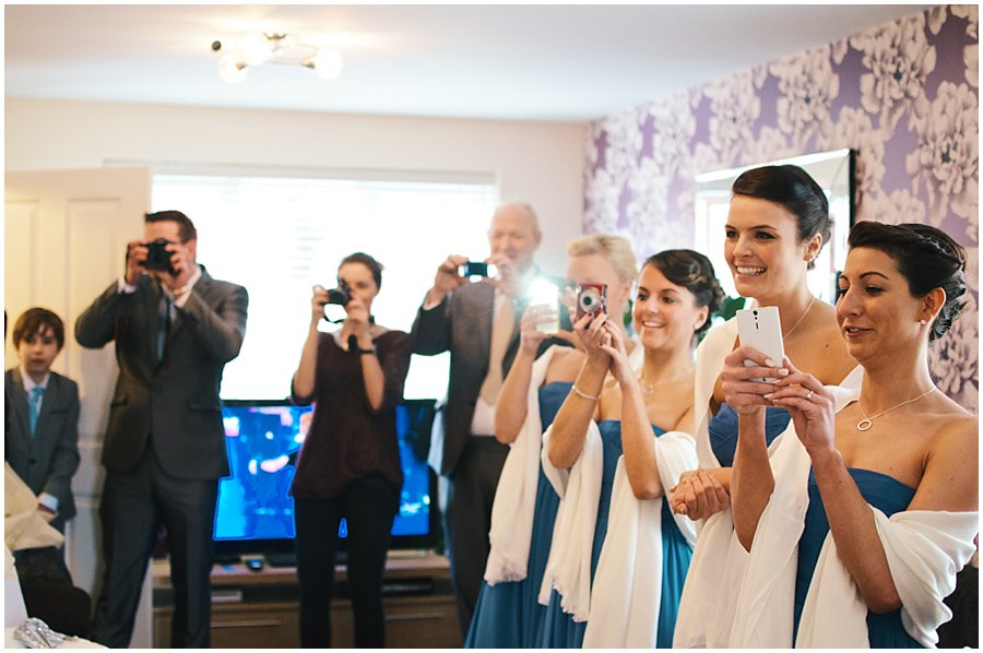 bridesmaids and family taking photos of bride as she comes downstairs