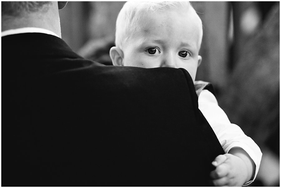 boy peeking over his father's shoulder at a wedding in essex