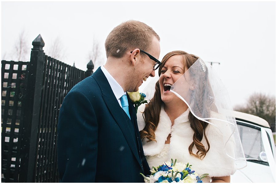 bride and groom laughing in the snow at Crondon Park