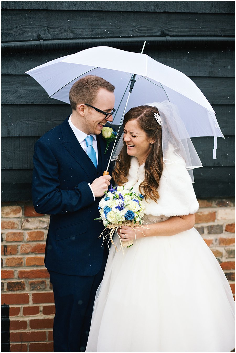 bride and groom laughing under an umbrella in the snow at Crondon Park