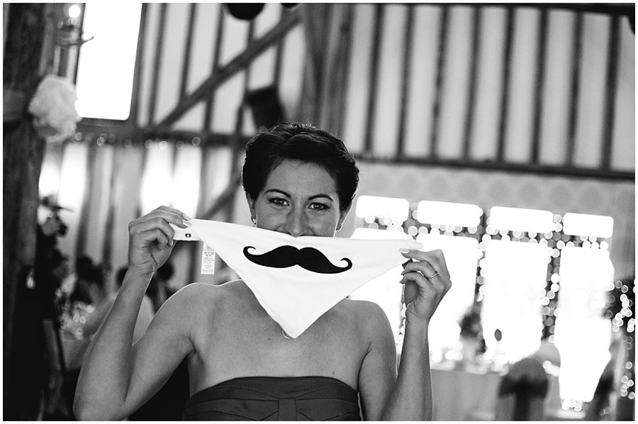 bridesmaid holding up a moustache bib in front of her mouth