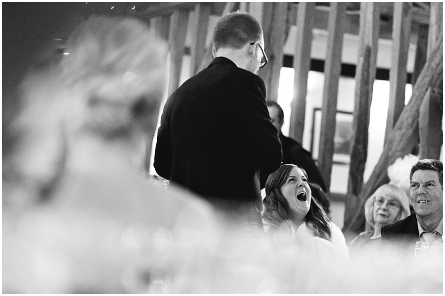 bride laughing during groom's speech.