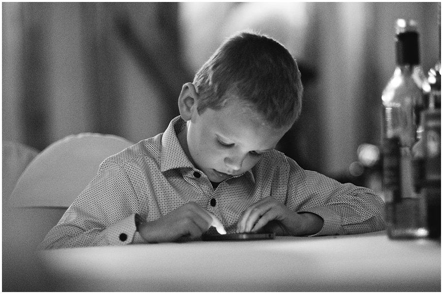 boy playing on an iphone during a wedding