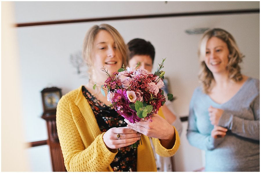 bride's family showing her her bouquet on her wedding day