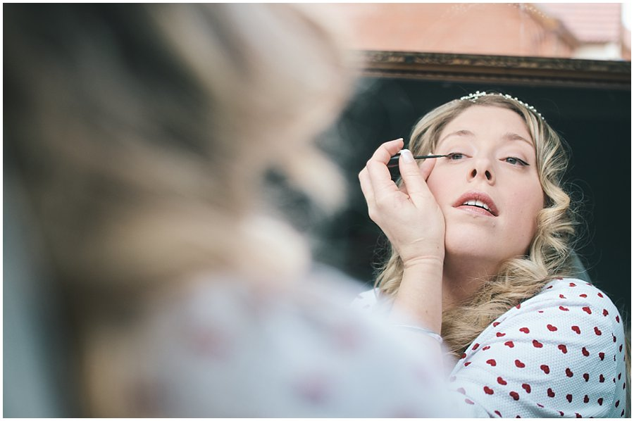 bride applying her make up before her wedding at red brick barn