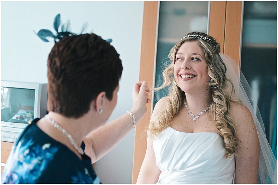 bride smiling with her mother before her wedding at red brick barn