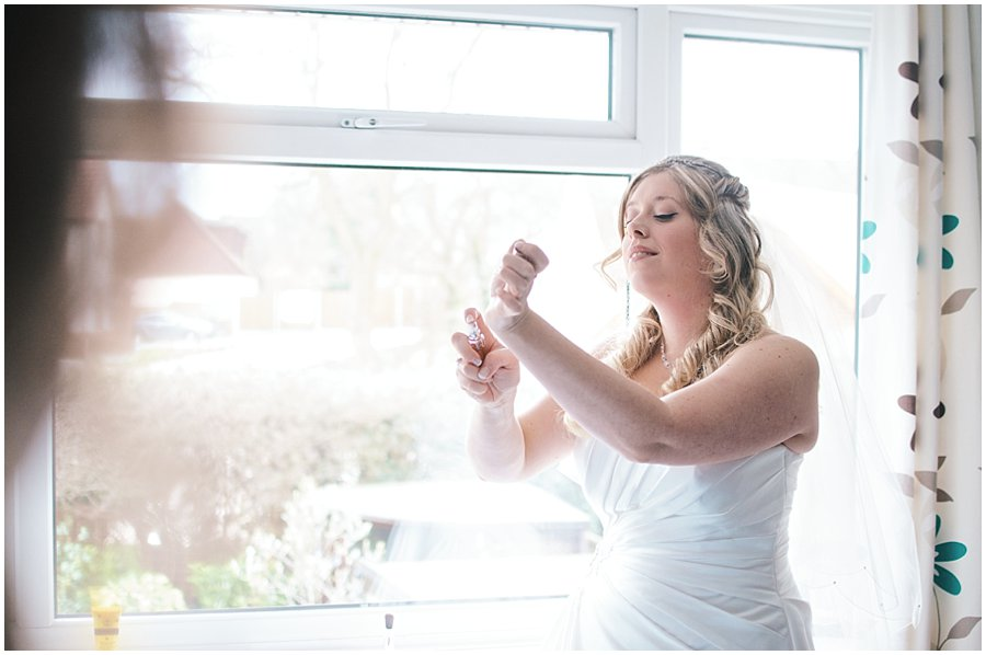 bride putting perfume on before her wedding