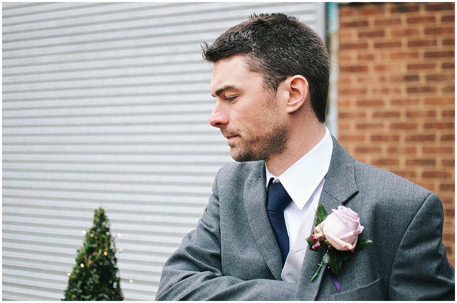 groom waits for his guests outside red brick barn in rochford