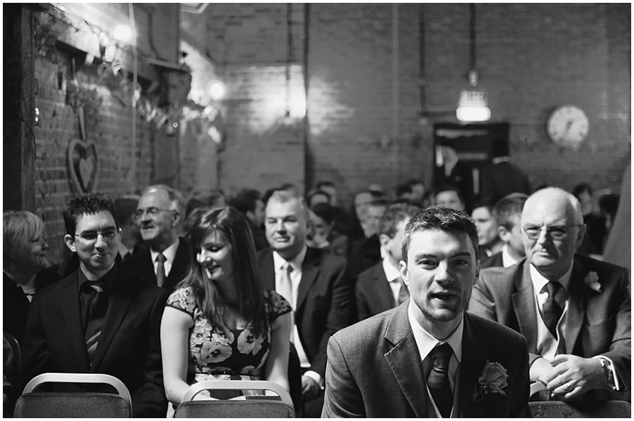 groom and his guests wait for the bride at red brick barn in rochford