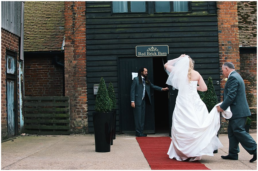 bride walking into red brick barn with her father
