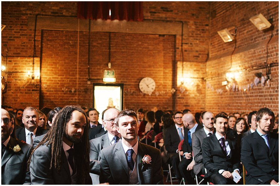 groom waits nervously for his bride at red brick barn