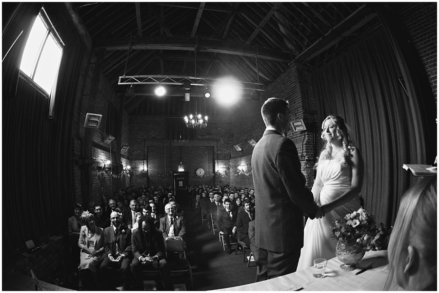 bride and groom taking their vows at red brick barn, rochford