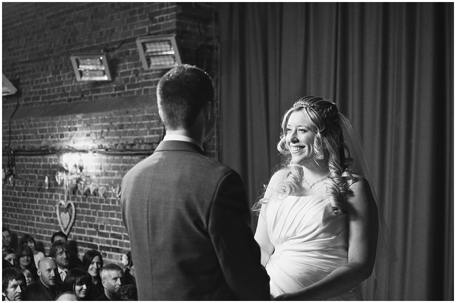 bride and groom smiling whilst taking their vows at red brick barn near rochford