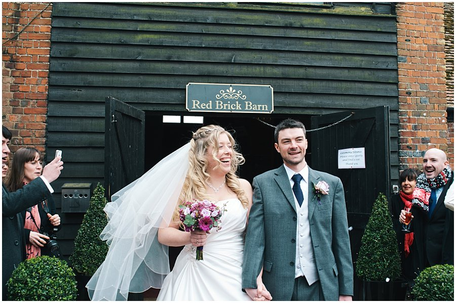 bride and groom leaving their ceremony at red brick barn near rochford