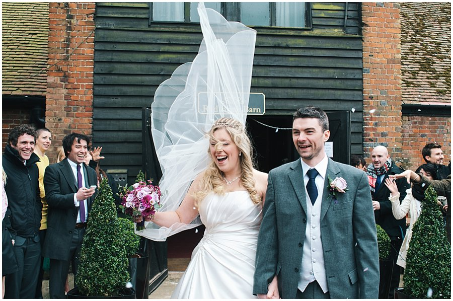 bride and groom having confetti thrown at them whilst the wind catches the bride's veil
