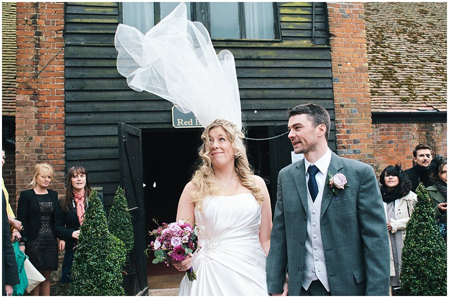 wind catching a bride's veil at red brick barn