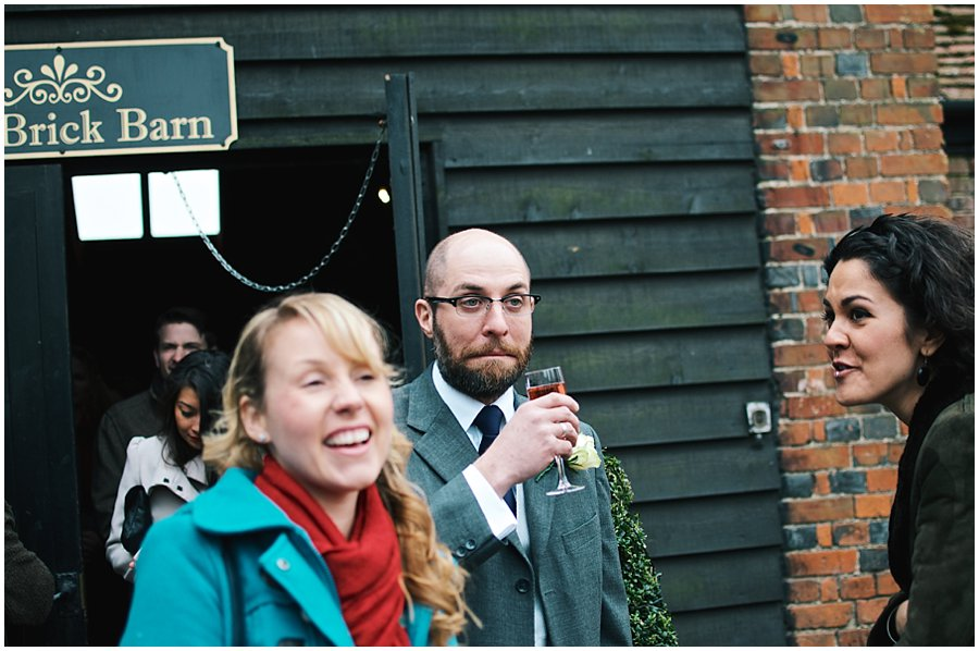 guests drinking champagne outside red brick barn near rochford