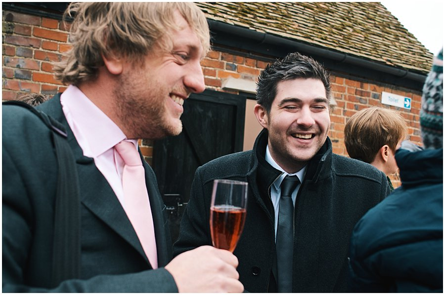 guests drinking champagne outside red brick barn