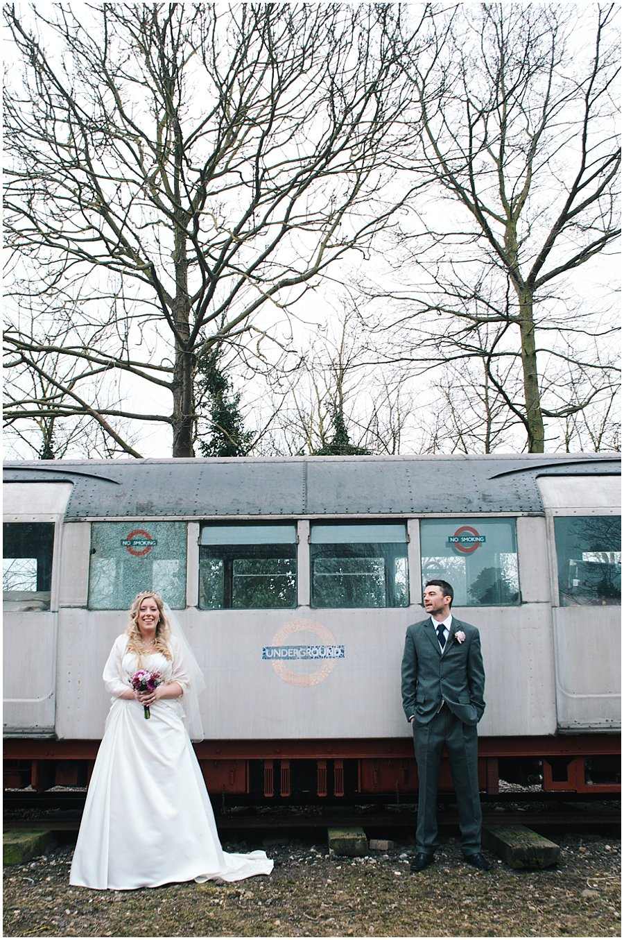 bride and groom portrait in front of an old tube train at red brick barn near rochford