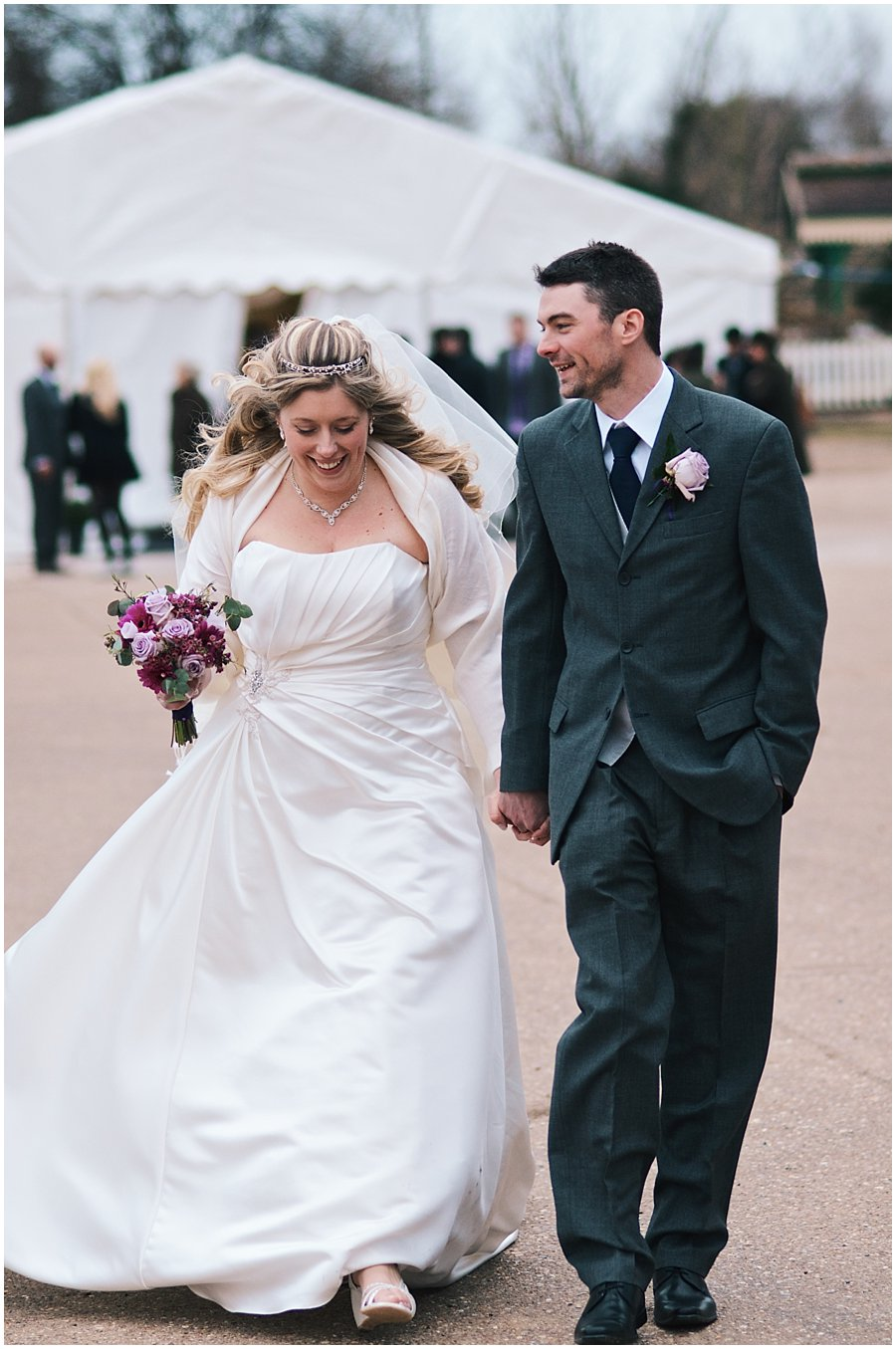 bride and groom walking together at red brick barn