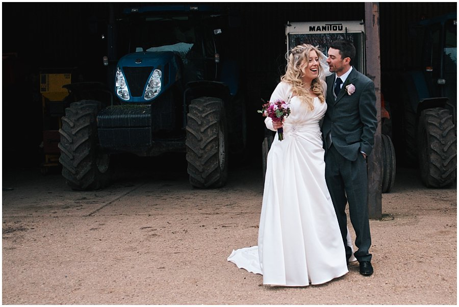 bride and groom portrait with tractors at red brick barn
