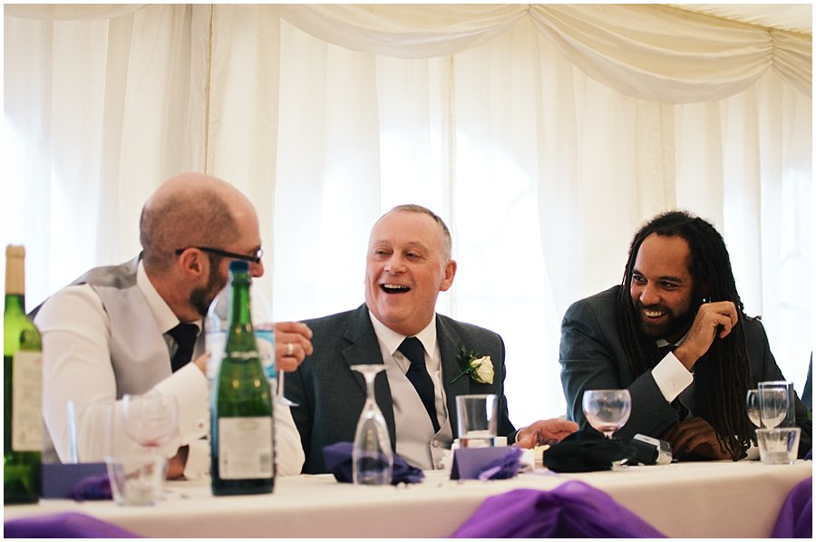 best men and father of the bride laughing at red brick barn