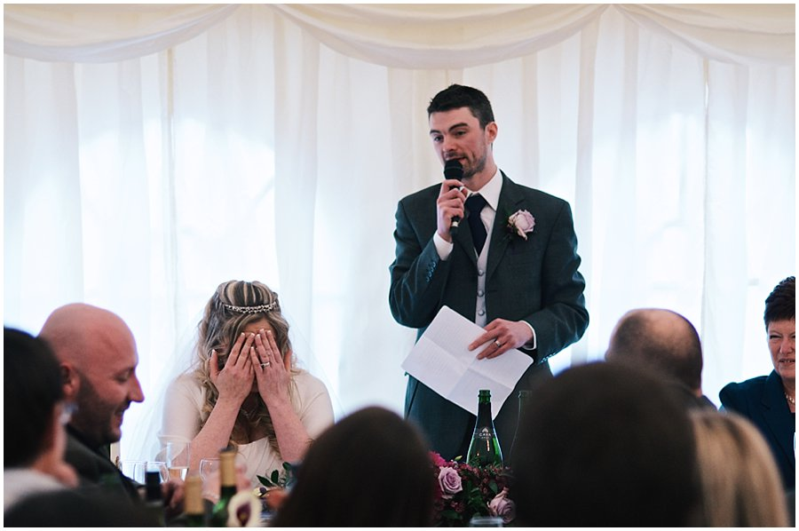groom making his speech at red brick barn whilst bride covers her face