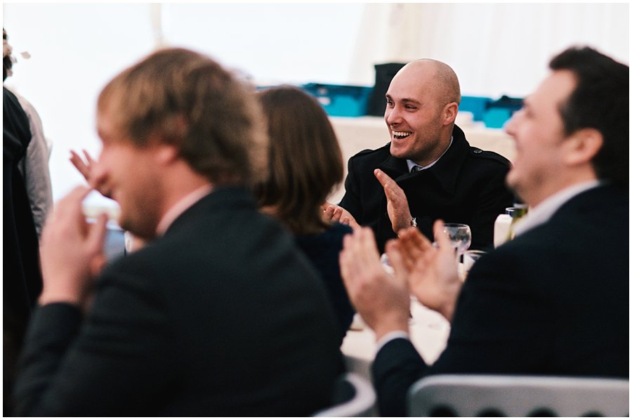 wedding guest smiling and clapping during speeches