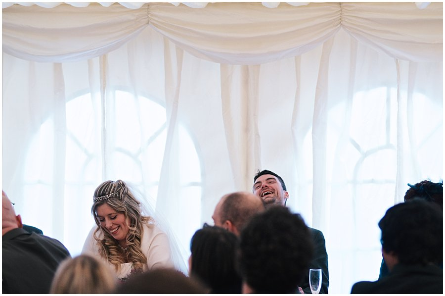 bride and groom laughing during the best man's speech