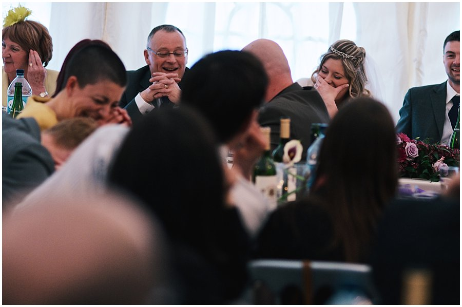 bride, groom and guests laughing during the best man's speech