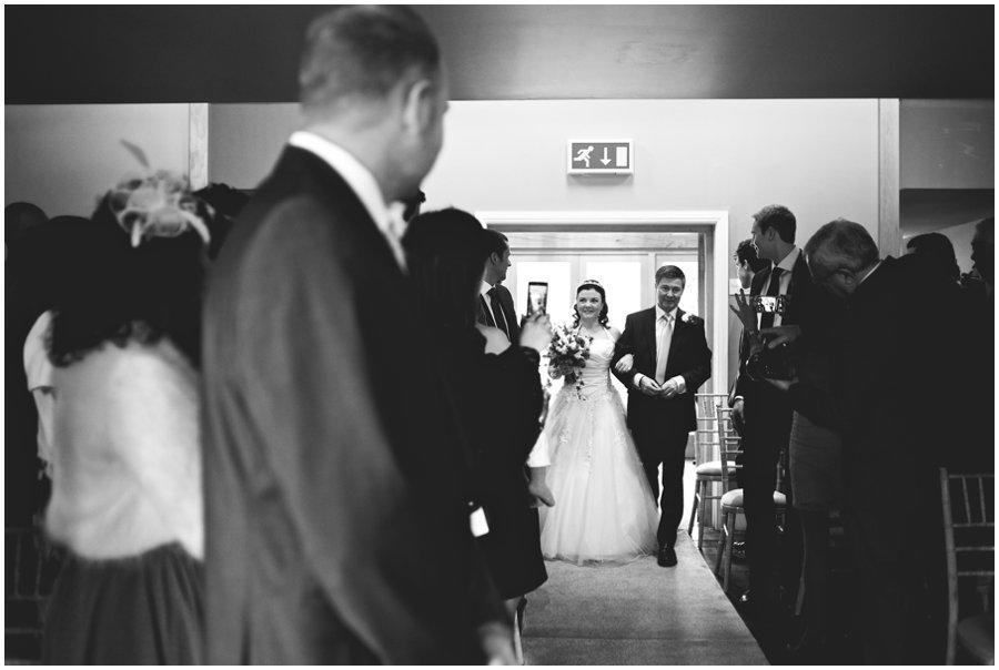 bride walks down the aisle at hyde barn