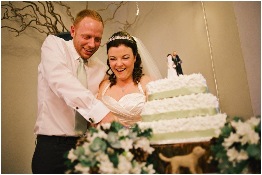 bride and groom cut cake at hyde barn wedding
