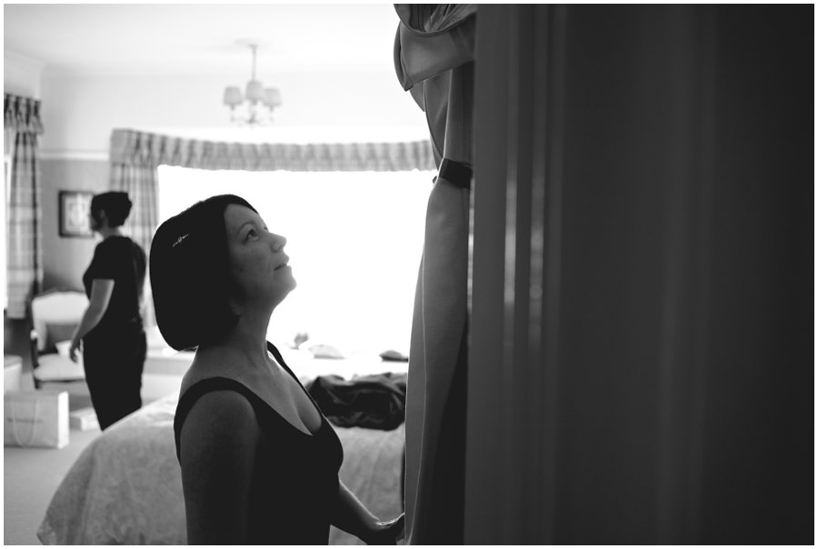 Bride looking at her dress hanging on a door