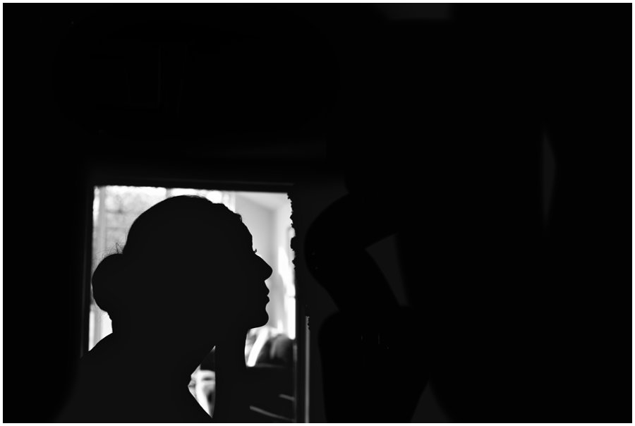 silhouette of bride putting on make up