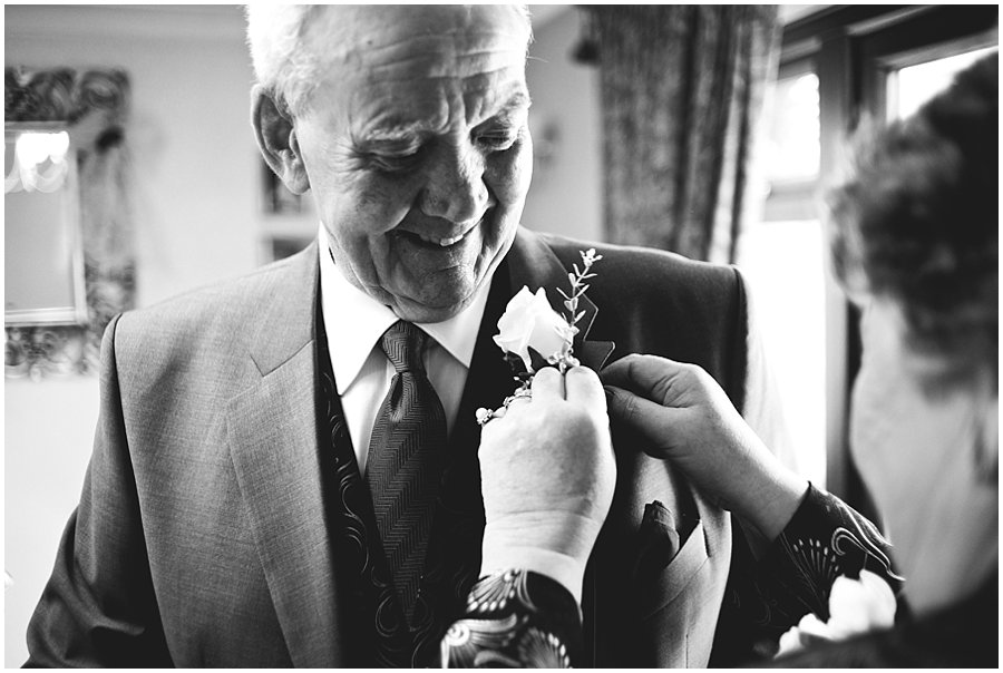 button hole being pinned on granddad before wedding in Essex