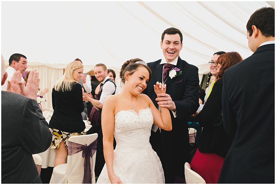 Bride and groom enter marquee at Newland Hall Wedding
