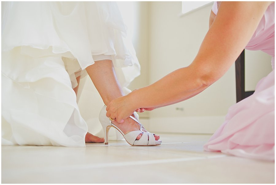 bridesmaid helping bride putting her shoes on
