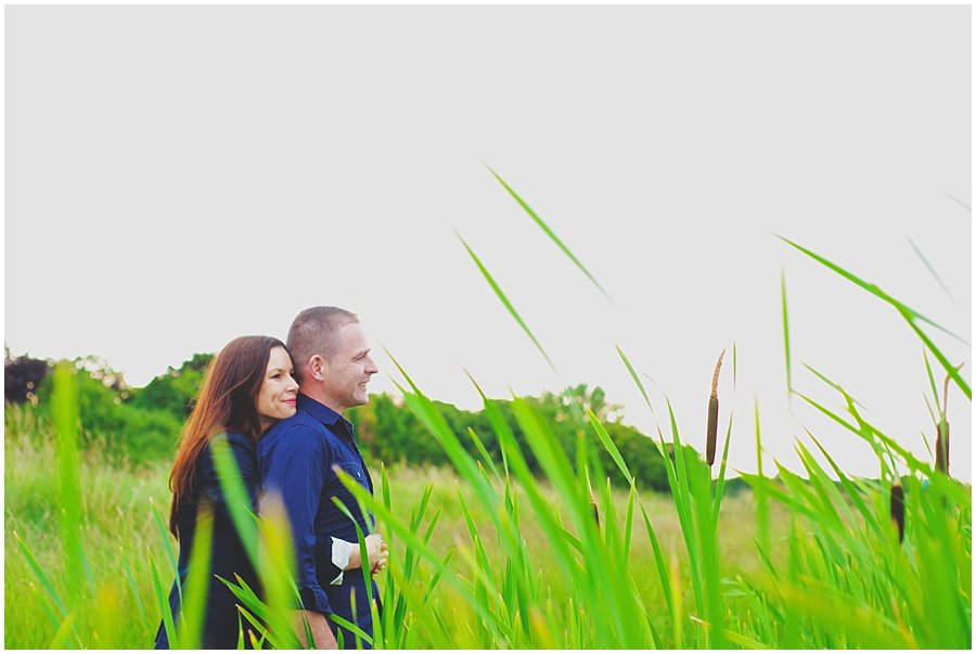 couple cuddling in the reeds on their engagement shoot at shoebury garrison