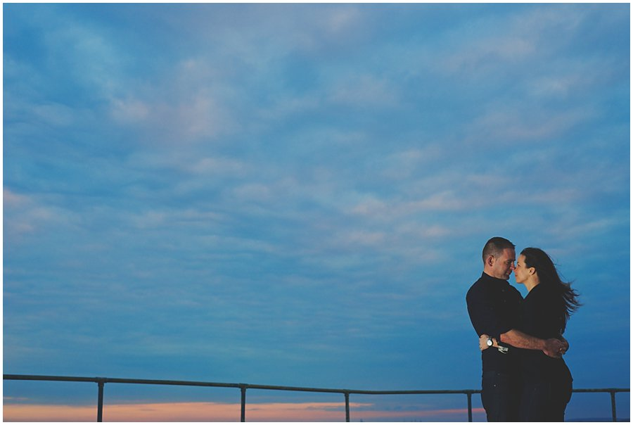 couple standing on new barge pier at sunset