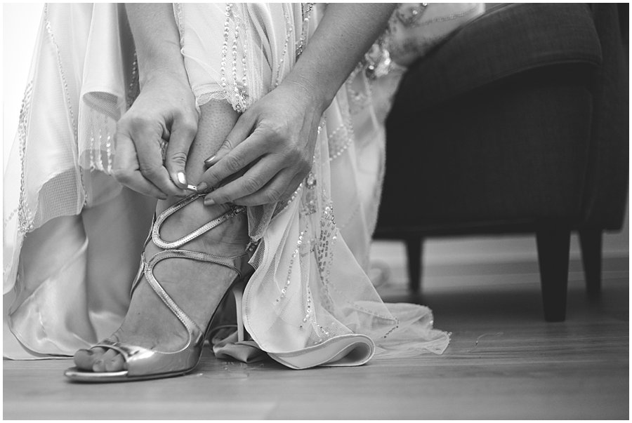 bride putting on Jimmy Choo wedding shoes