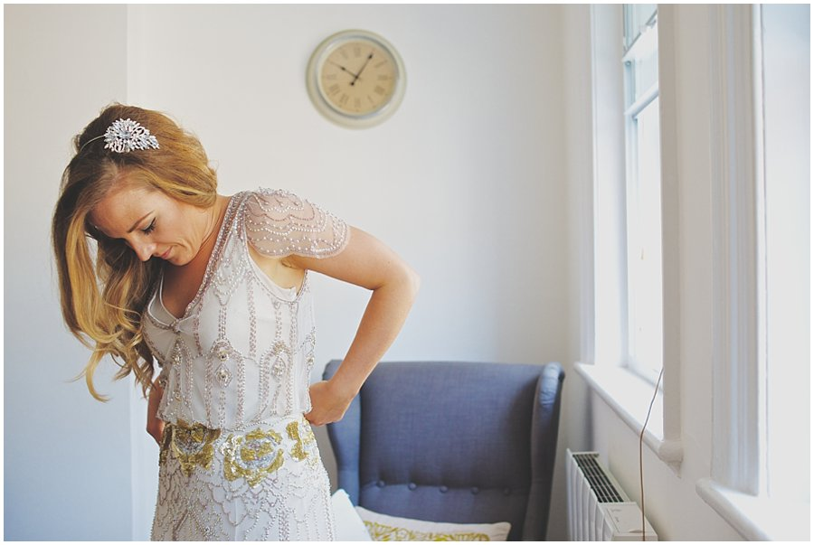 Bride putting on Jenny Packham dress