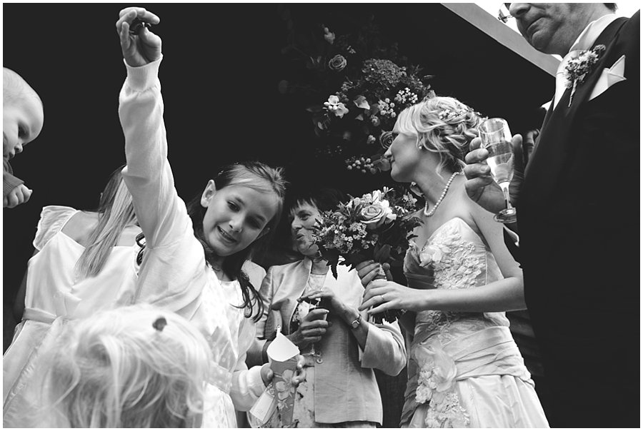 Flower girl sprinkling petals at Gate Street Barn