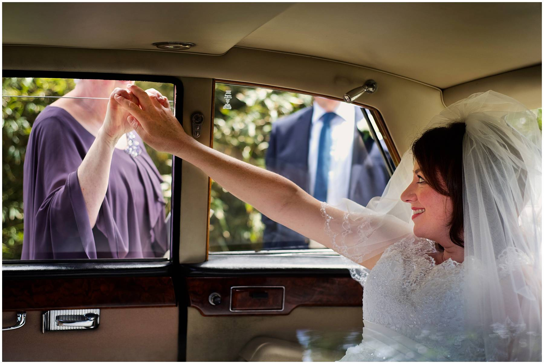Bride and her mum holding hands in wedding car