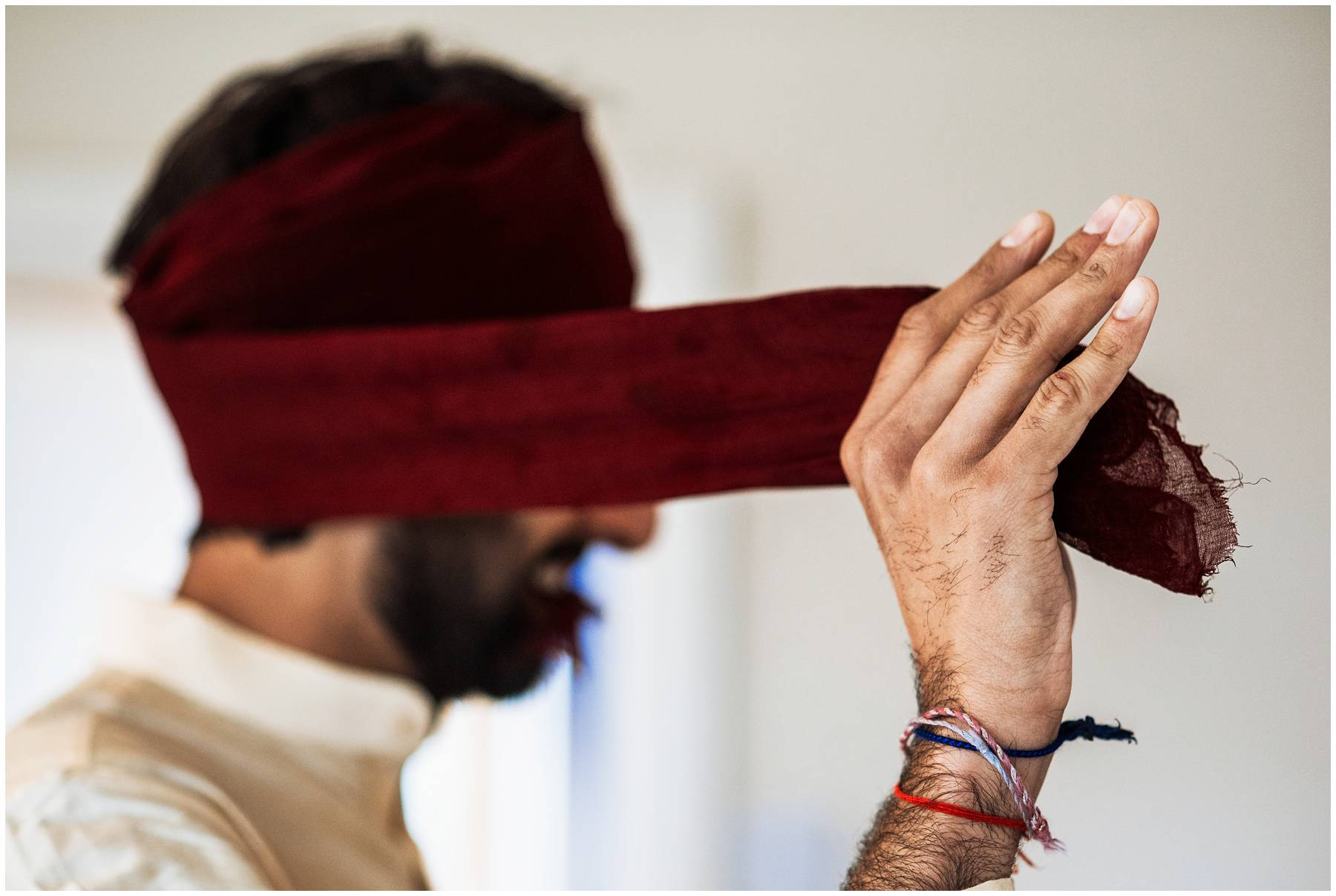 Sikh groom putting on wedding turban