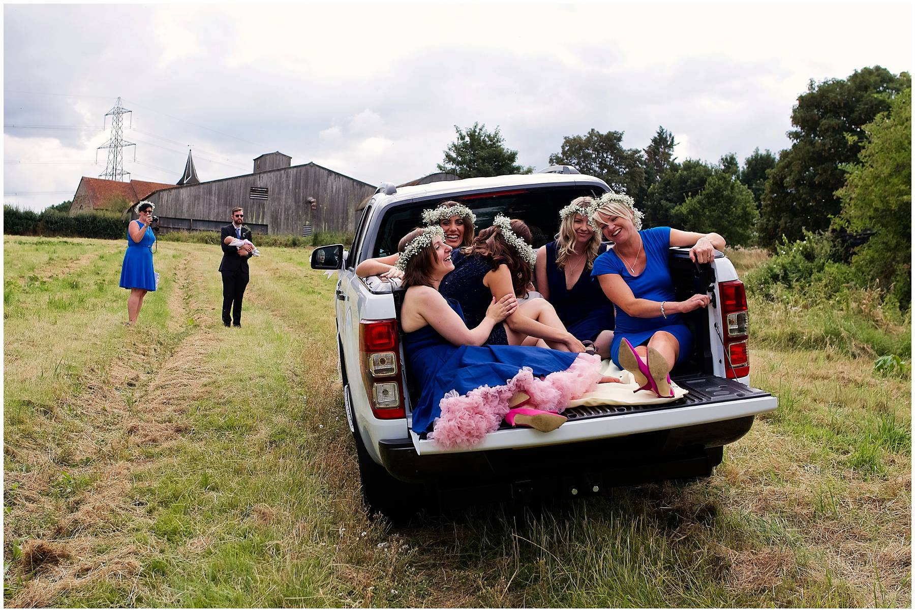 Bridesmaids in pick up truck at Essex farm wedding