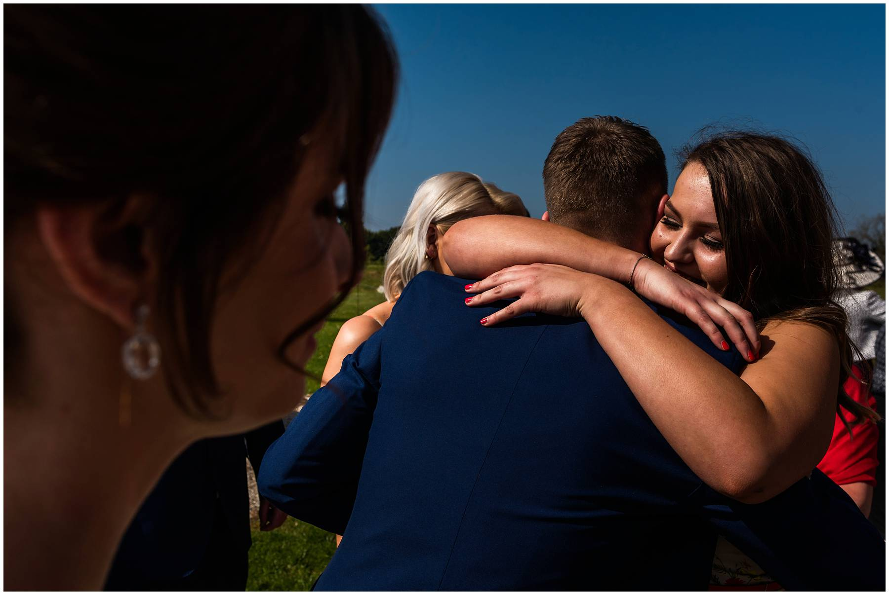 Bridesmaid hugging groom at The Winding House