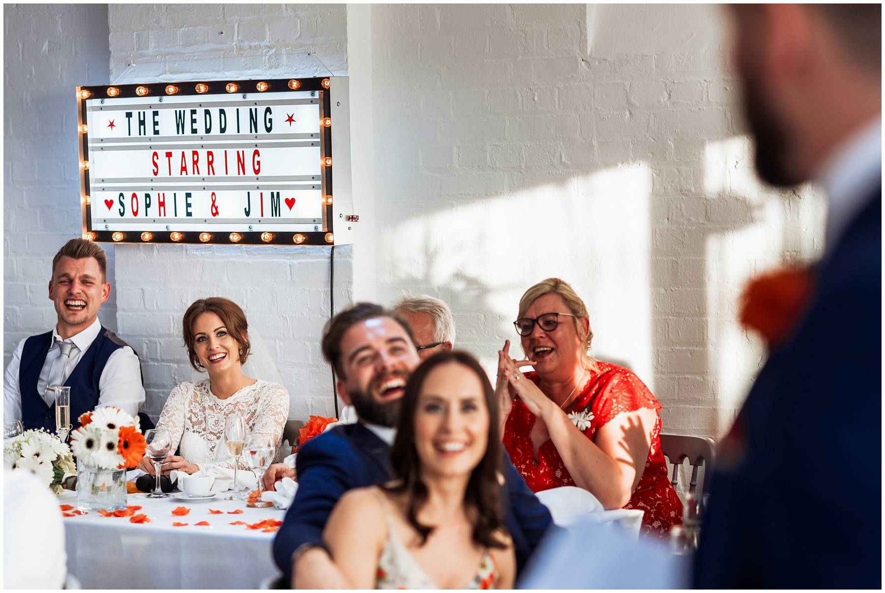 Bride, groom and guests laughing at The Winding House Wedding